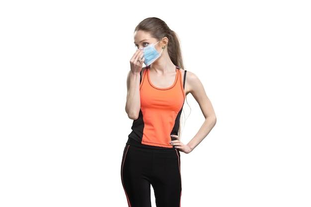Wijfje in een gezichtsmasker en een oranje sportkostuum dat uitwerkt