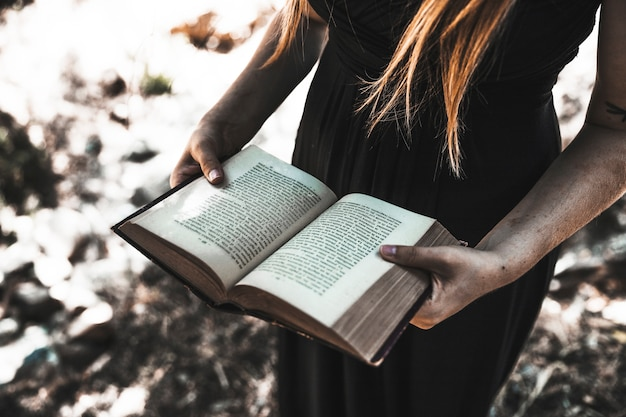 Wijfje in kleding die geopend boek in houtdag houden