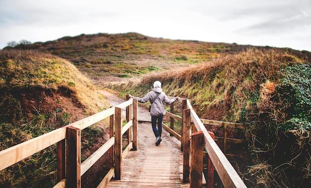 Wijfje op een houten promenade over de aard