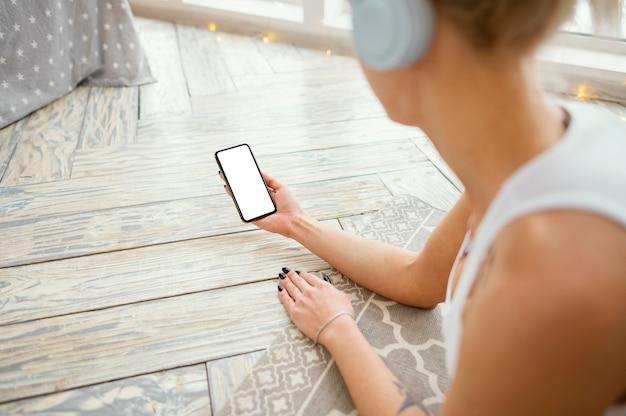 Wijfje op mat met hoofdtelefoons die telefoon met behulp van