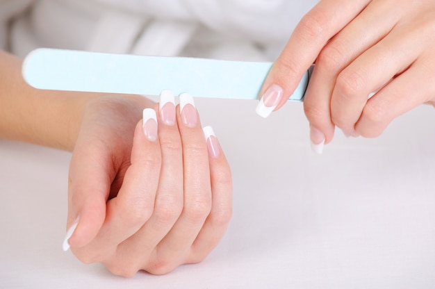 Wijfje polijsten haar vingernagels met een franse manicure