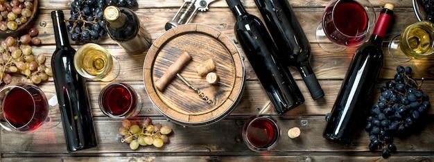 Wijn achtergrond. witte en rode wijn in glazen. op een houten achtergrond.