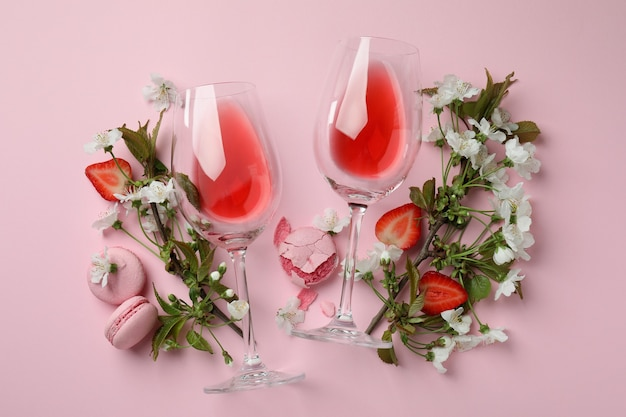 Wijn, bitterkoekjes, aardbei en bloemen op roze achtergrond