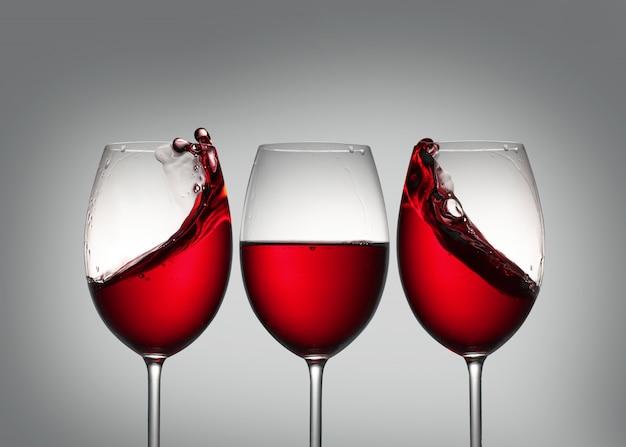 Wijn. drie glazen rode wijn met plons in zijglazen die symmetrie vormt.