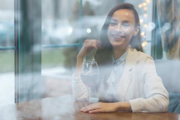 Wijn drinken. vrolijke mooie onweerstaanbare vrouw die met haar speelt terwijl ze naar de camera staart en een glas wijn aanraakt