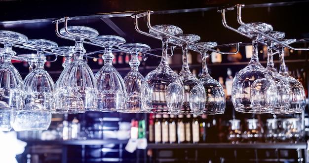 Wijn en martini-glazen in plank boven een barrek in restaurant.