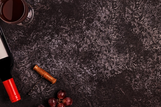 Wijn, glazen, druiven en kurkentrekker over steen
