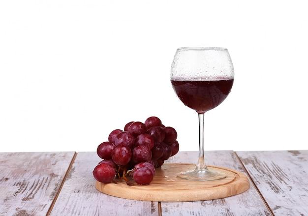Wijn het gieten in glas met druif en geïsoleerde flessen