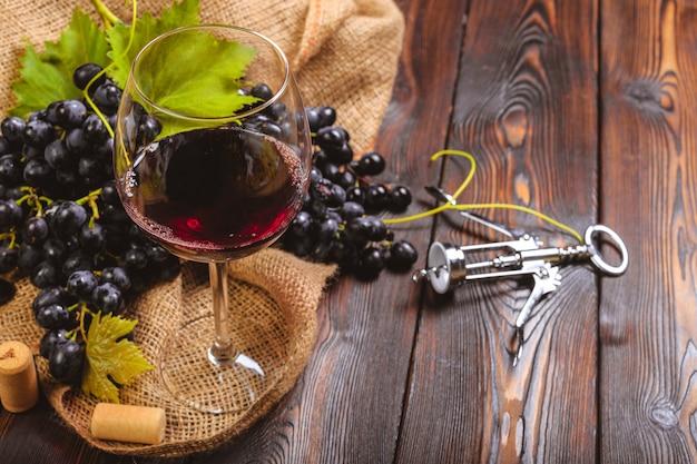 Wijn met takken van witte druiven. op een houten tafel.