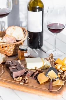 Wijn, stokbrood en kaas op houten achtergrond