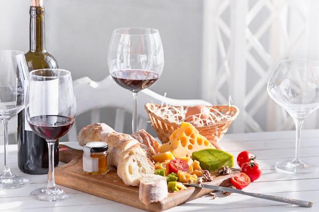 Wijn, stokbrood en kaas op houten tafel