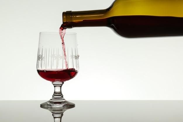 Wijn stroomt uit een fles in een glas