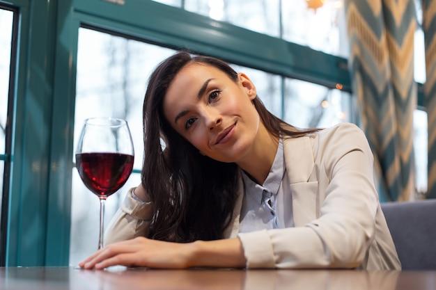 Wijn tijd. aangename jonge brunette vrouw haar aan te raken tijdens het plaatsen van de hand op tafel en het drinken van wijn