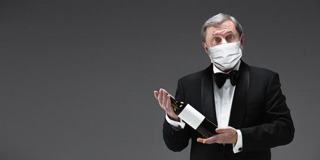 Wijn voorstellen. elegantie senior man ober in beschermend masker op grijze achtergrond. flyer met copyspace. café, restaurantopening. veiligheid tijdens een pandemie van het coronavirus. verzorgen van gasten, klanten.