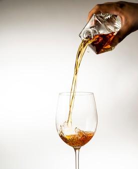 Wijn wordt in een glas op een lichte achtergrond gegoten