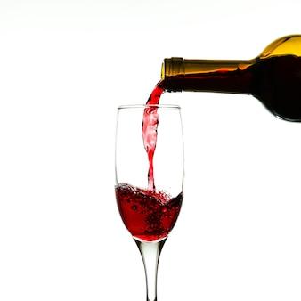 Wijn wordt uit een fles in een glas gegoten