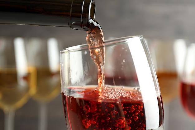 Wijn wordt uit fles in een glas gegoten, close-up en selectieve focus