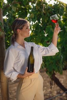 Wijnboervrouw die rode wijn proeft van een glas in een wijngaard. wijngaarden achtergrond bij zonsondergang.