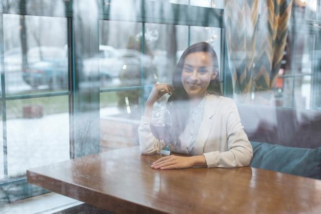 Wijnconsumptie. charmante oprechte jonge vrouw zittend aan tafel tijdens het kijken naar camera en betalen met haar