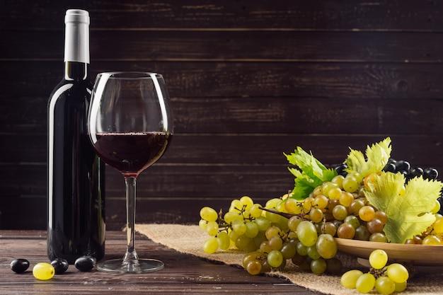 Wijnfles en druif op houten tafel
