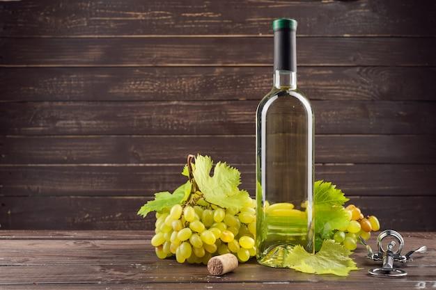 Wijnfles en druivenmost op houten tafel