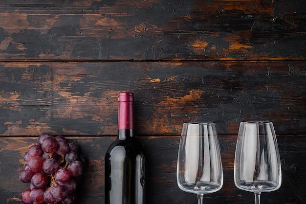 Wijnfles met druiven set, op oude donkere houten tafel, bovenaanzicht plat lag