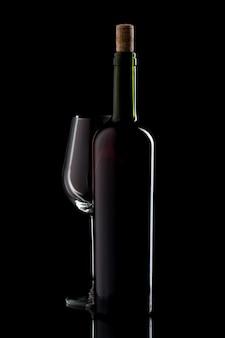 Wijnfles met kurk en leeg glas op geïsoleerde zwarte