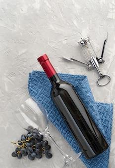 Wijnfles, wijnglas, tros blauwe druiven en kurkentrekker op grijze gestructureerde achtergrond. plat leggen. bovenaanzicht. ruimte kopiëren.