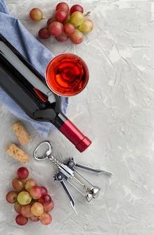 Wijnfles, wijnglas, trossen roze druiven en metalen kurkentrekker op grijze gestructureerde achtergrond met kopieerruimte voor uw tekst. plat leggen. bovenaanzicht.