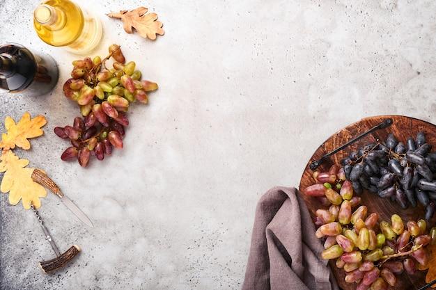 Wijnflessen met druiven en wijnglazen op oude grijze betonnen tafelachtergrond met kopieerruimte. rode wijn met een wijnstoktak. wijnsamenstelling op rustieke achtergrond. bespotten.