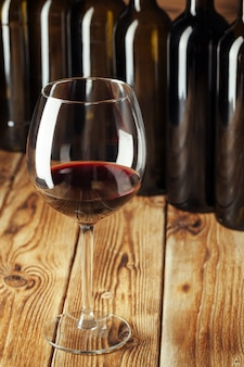 Wijnflessen met glas, houten achtergrond