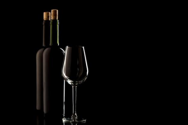 Wijnflessen met kurk en glas op zwarte geïsoleerde achtergrond