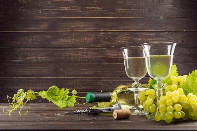 Wijnglas en tros druiven op houten tafel