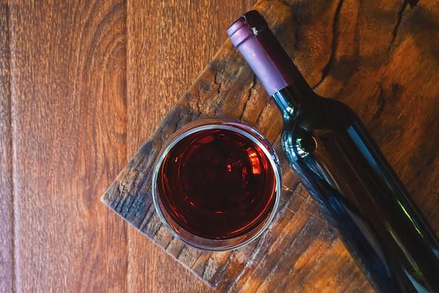 Wijnglas en wijnfles op de houten tafel