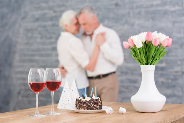 Wijnglas; feesthoed; verjaardagstaart en bloemenvaas op tafel aan de voorkant wazig paar dansen