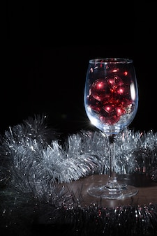 Wijnglas gevuld met kerstballen. op een zwarte achtergrond.