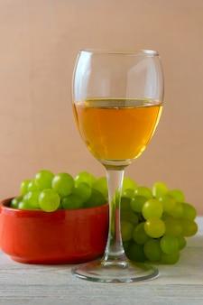 Wijnglas, groene druiven op plaat op tafel.