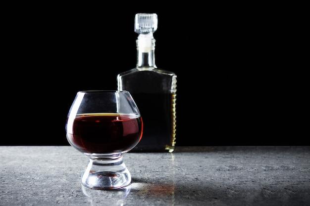 Wijnglas met donkere alcohol op grijze granieten tafel op zwarte achtergrond met fles.