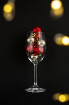 Wijnglas met rode en gouden kerstballen op de zwarte achtergrond. detailopname. locatie verticaal.