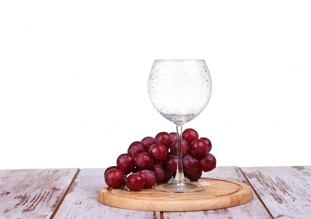 Wijnglas met rode wijn, fles wijn en druiven geïsoleerd op witte achtergrond
