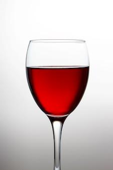 Wijnglas met rode wijnclose-up dat op lichte gradiënt wordt geïsoleerd