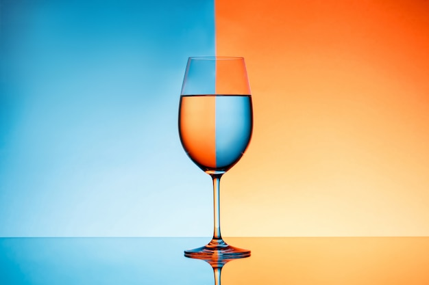 Wijnglas met water over blauwe en oranje achtergrond.