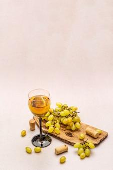 Wijnglas, verse druiven en kurken op houten snijplank. wijnbar, wijnmakerij, wijnproeverij concept.