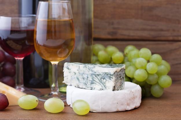 Wijnglazen dichtbij kaas en rijpe druif op houten dek