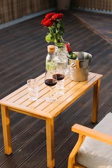 Wijnglazen en ijsemmer met wijnfles op houten lijst bij terras