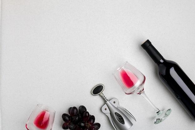 Wijnglazen en kurkentrekker over witte achtergrond bovenaanzicht