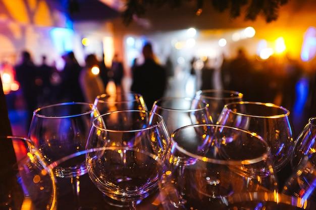 Wijnglazen in de schittering van licht op vage silhouetten van mensenachtergrond