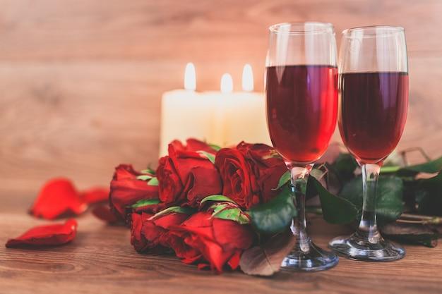 Wijnglazen met brandende kaarsen en een boeket rozen
