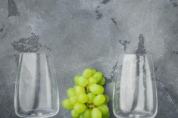 Wijnglazen met druiven set, op grijze stenen tafel, bovenaanzicht plat lag
