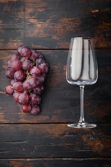 Wijnglazen met druiven set, op oude donkere houten tafel, bovenaanzicht plat lag